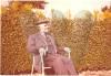 Anders Andersen siddende i stol i haven